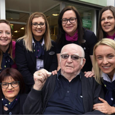 A team of Optical Assistants helping an elderly man at a Specsavers store